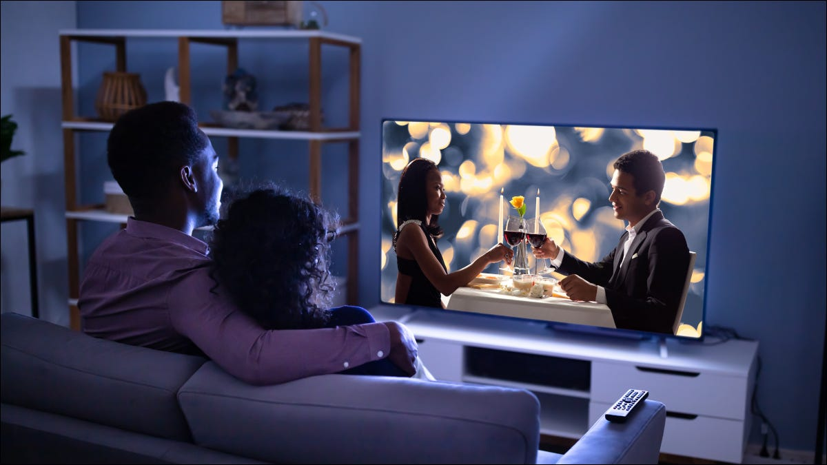 Young couple watching a movie on a large TV in a modern home
