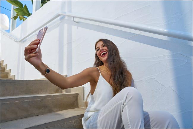 Young Latin woman smiling and looking up to take a selfie