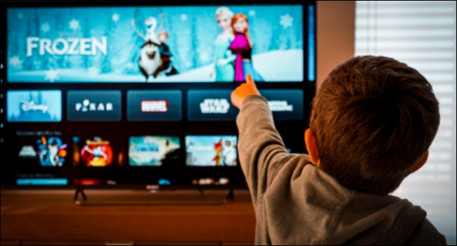 child pointing at TV with Disney+ on it