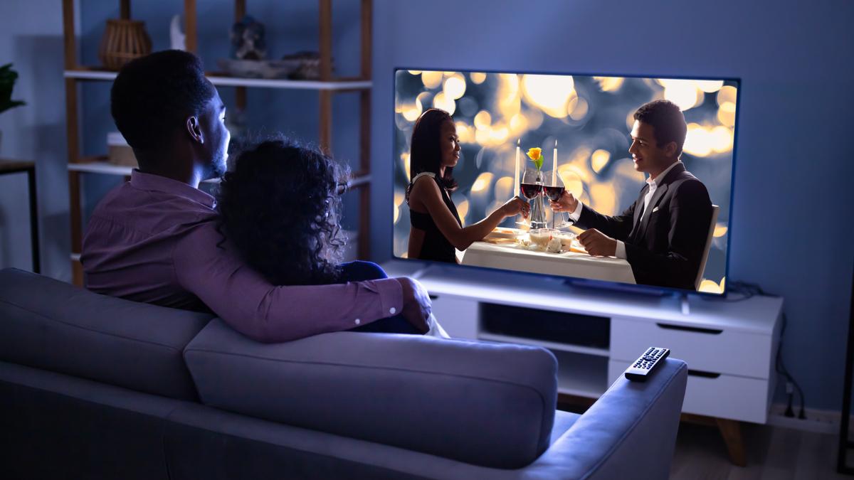 couple watching romantic movie in darkened room