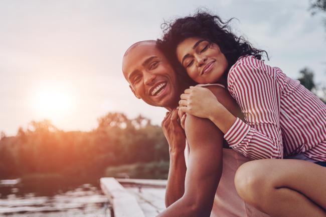 Um casal se abraçando e parecendo feliz na doca de um lago