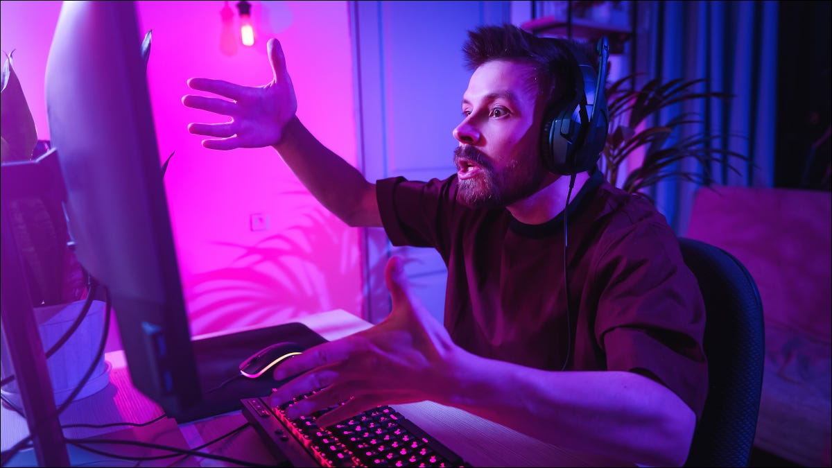 Male gamer looking upset at computer screen