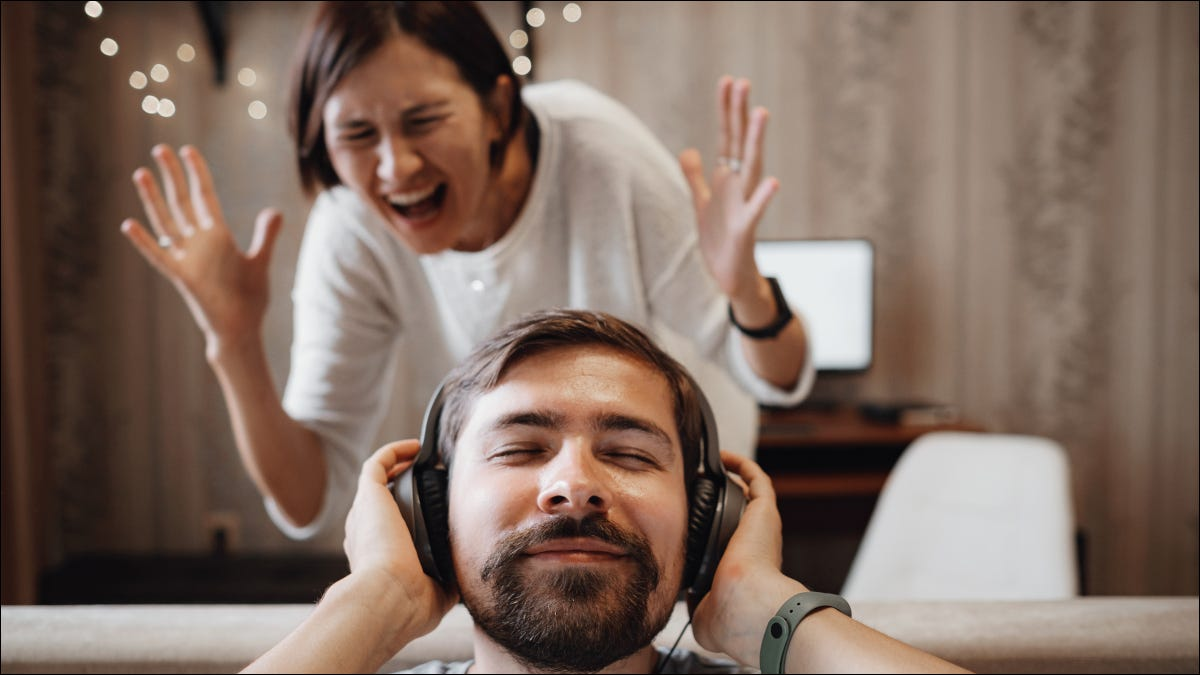 Man wearing headphones with a smile while a woman screams with anger.