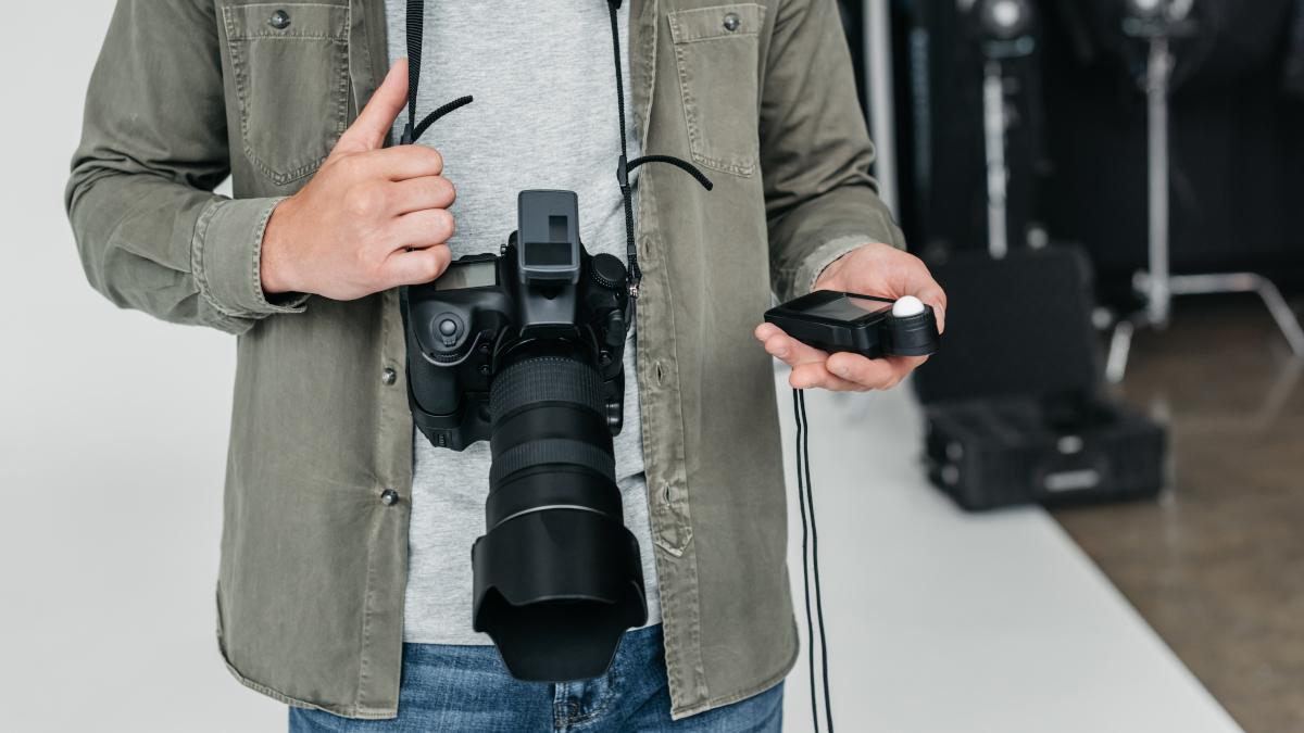 Photographer using a light meter in photo studio