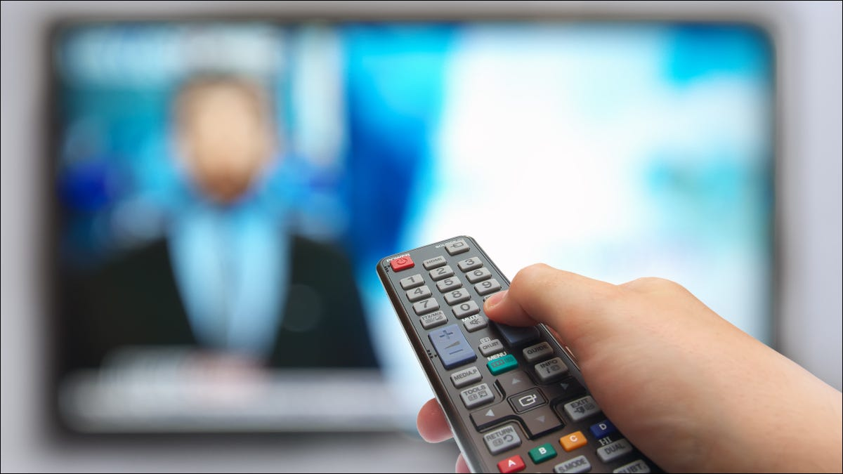 Closeup of a hand holding a remote in front of a TV screen