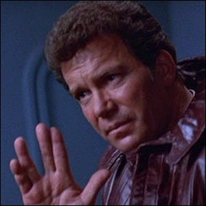 William Shatner performing the Vulcan salute, assisted by fishing line