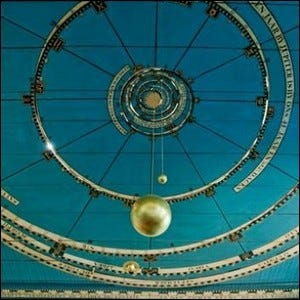 Photograph depicting the teal and golden mechanical components of the planetarium